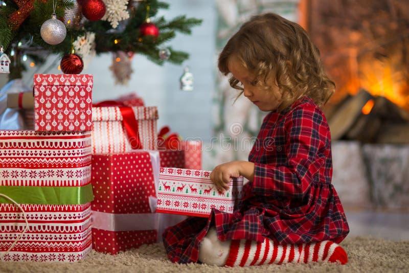 Het meisjeskind viert thuis Kerstmis door de open haard en Chr stock fotografie