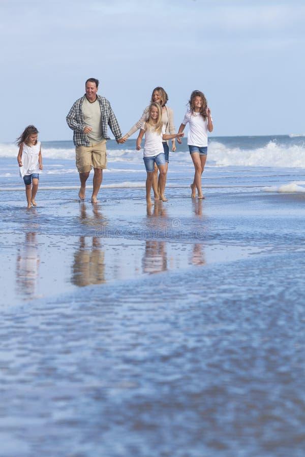 Het Meisjeskinderen die van familieouders op Strand lopen stock foto