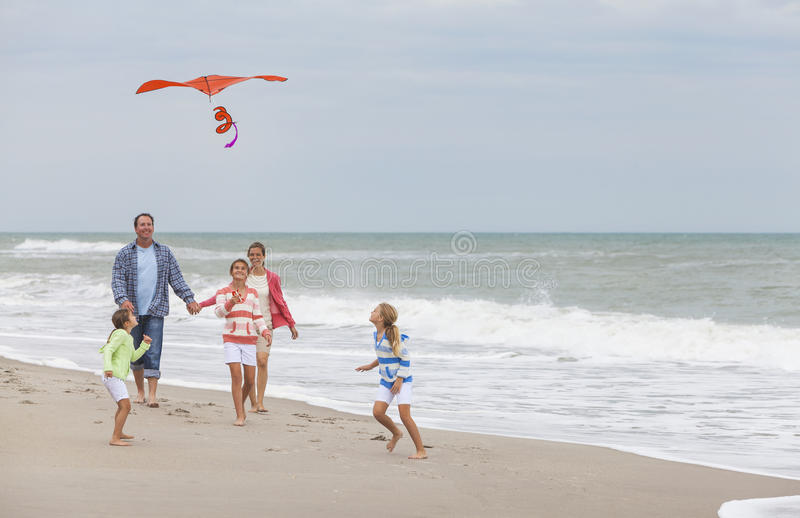 Het Meisjeskinderen die van familieouders Vlieger op Strand vliegen stock foto's