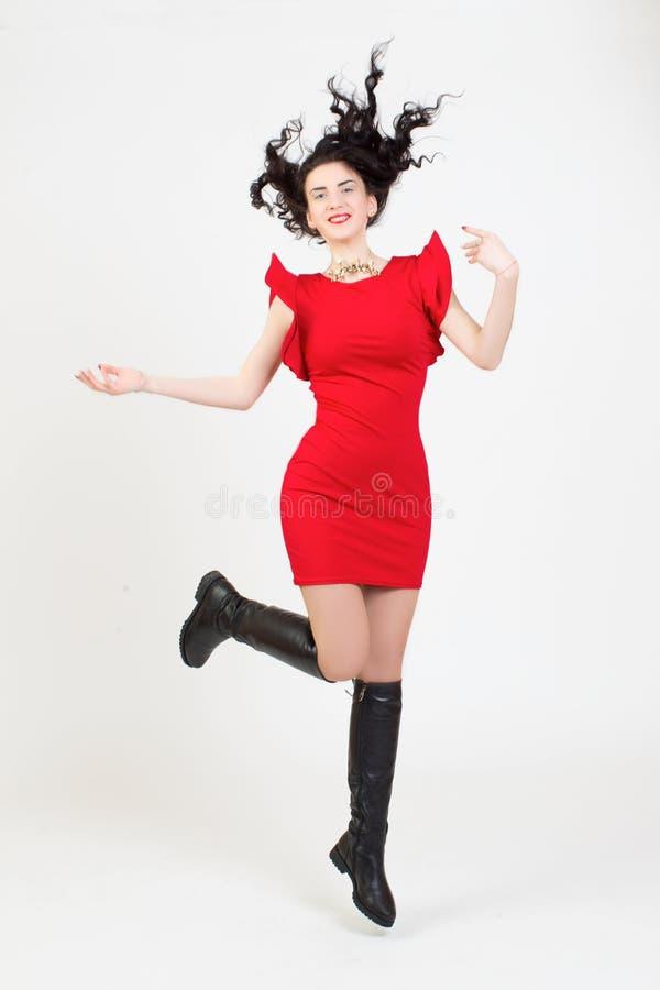 Het meisjesmodel in heldere rode kleding springt omhoog royalty-vrije stock foto's