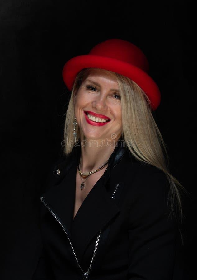 Het meisjesmodel met wit haar in een rode hoed met rode lippenstift lacht studiofoto stock fotografie