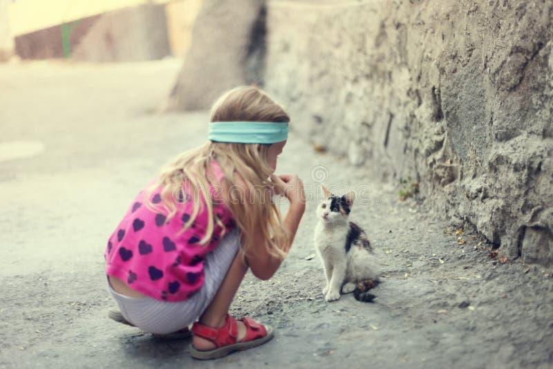 Het meisjespelen van de blonde met katje royalty-vrije stock afbeelding