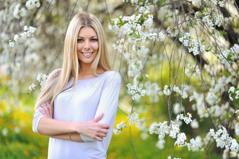 Het meisjesportret van de schoonheidslente over bloeiende boom met bloemen stock fotografie