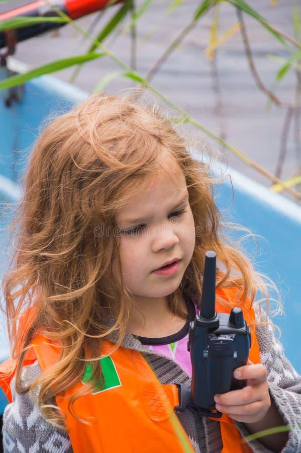 Het meisjesreddingsvest, een kind in een boot, zegt op de radio stock foto's