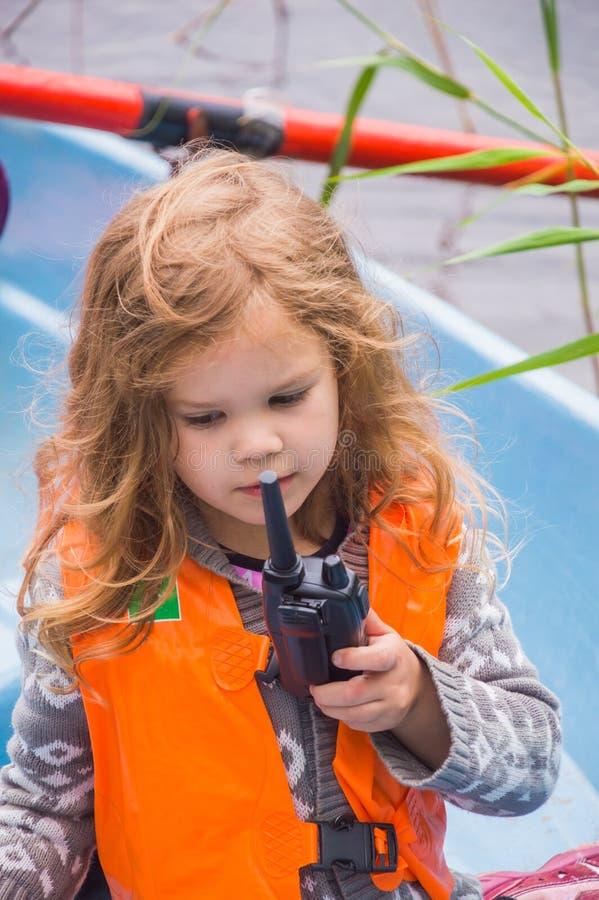 Het meisjesreddingsvest, een kind in een boot, zegt op de radio stock fotografie