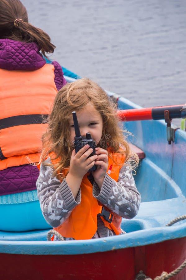 Het meisjesreddingsvest, een kind in een boot, zegt op de radio royalty-vrije stock fotografie