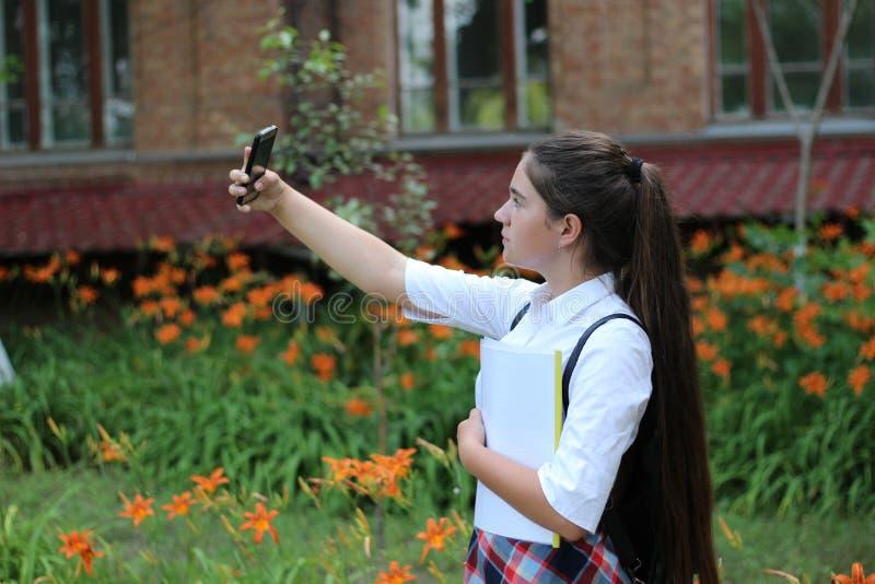 Het meisjesschoolmeisje met lang haar in eenvormige school maakt selfie stock fotografie