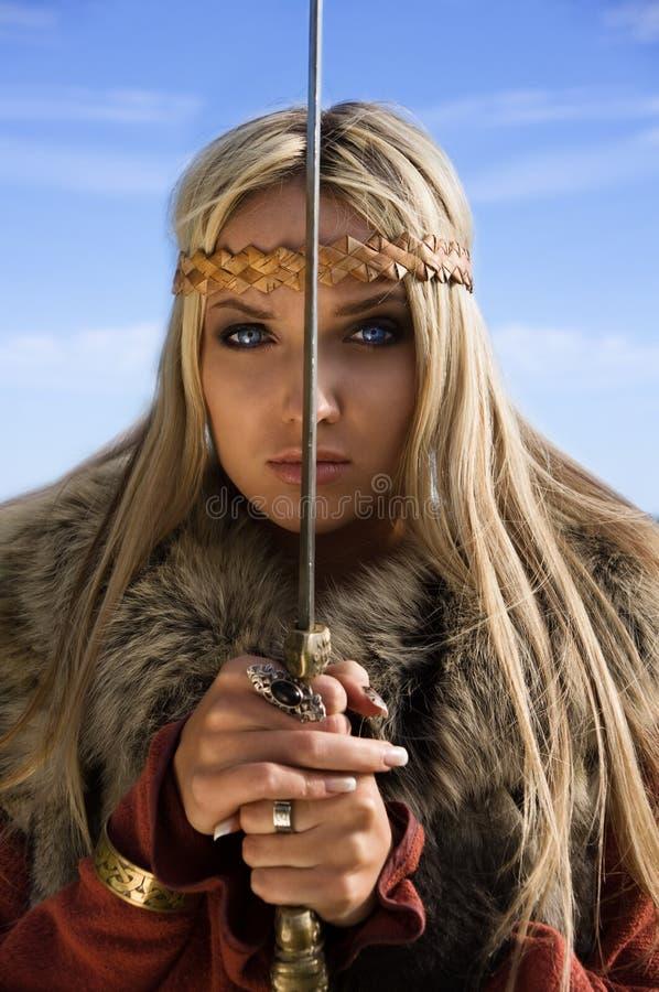 Het meisjesstrijder van Viking op een blauwe hemelachtergrond stock foto