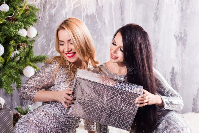 Het meisjesvrienden van de Kerstmisvakantie het gelukkige stelt ruilen in Kerstmis verfraaide woonkamer, santahoed van het slijta stock afbeelding
