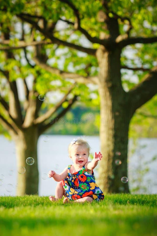 Het meisjeszitting van de blondepeuter in park met bellen stock fotografie