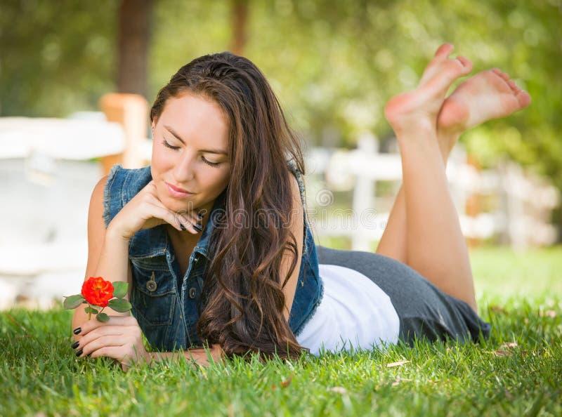 Het melancholie Gemengde Meisje die van de Rastiener in Gras met Bloem leggen royalty-vrije stock afbeeldingen