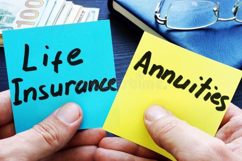 Het memorandumstokken van de mensenholding Levensverzekering versus annuïteiten stock foto