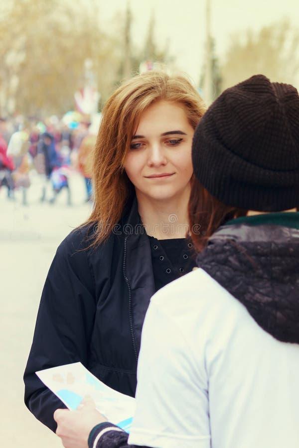 Het mengapparaat op de straat biedt een voorbijganger aan een meisje aan om een pamflet te nemen Agitatie, distributie van materi royalty-vrije stock afbeelding
