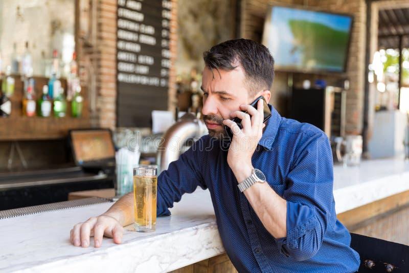 Het mengen van Alcohol met Telefoongesprek is een Gewaagd Spel royalty-vrije stock fotografie