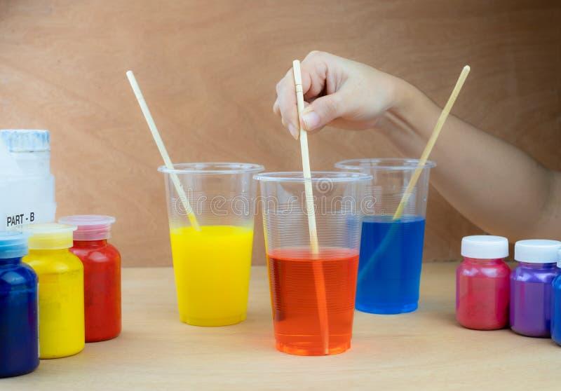 Het mengen van kleuren epoxyhars in plastic kop stock foto
