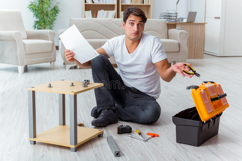 Het mens het assembleren meubilair thuis stock foto's