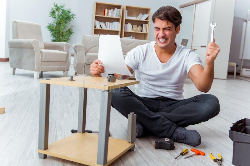 Het mens het assembleren meubilair thuis stock afbeeldingen