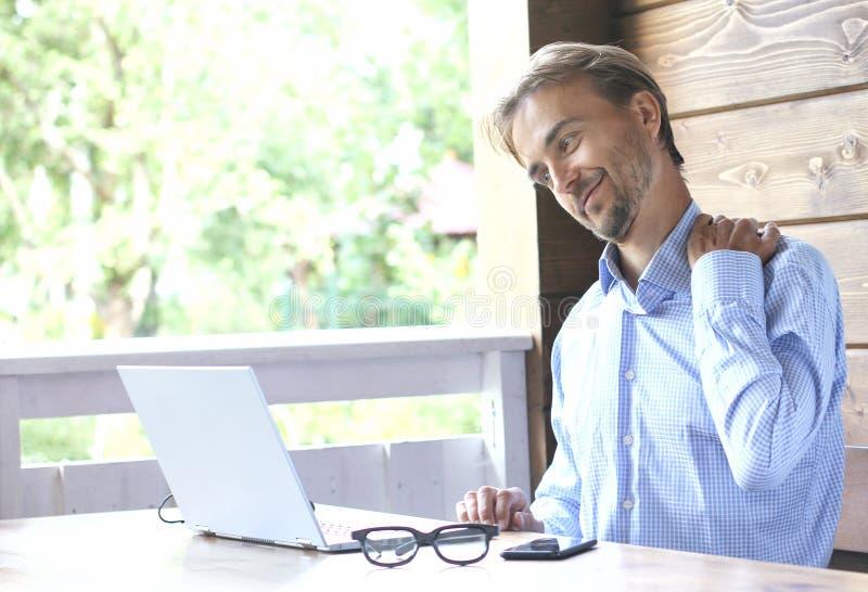 Het mensenwerk aangaande laptop op een open terras en feelsl pijn in zijn hals Het concept van het freelance of huisbureau stock foto's