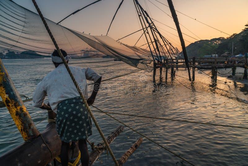Het mensenwerk bij Chinees visserij netsat Fort Kochi, stock afbeeldingen