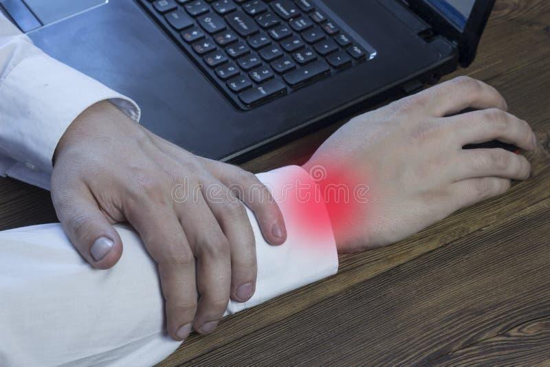 Het mensenwerk bij een computer en houdt zijn hand, kwetst zijn wapen, tunnelsyndroom royalty-vrije stock foto