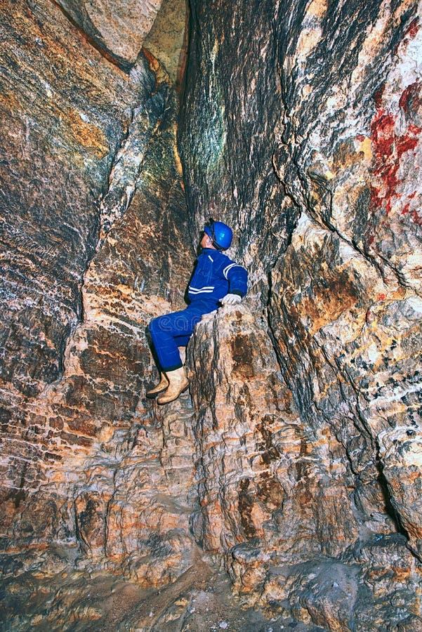 Het mensenwerk ondergronds in donkere tunnel Personeel in sedimenten van een de beschermende kostuumcontrole royalty-vrije stock fotografie