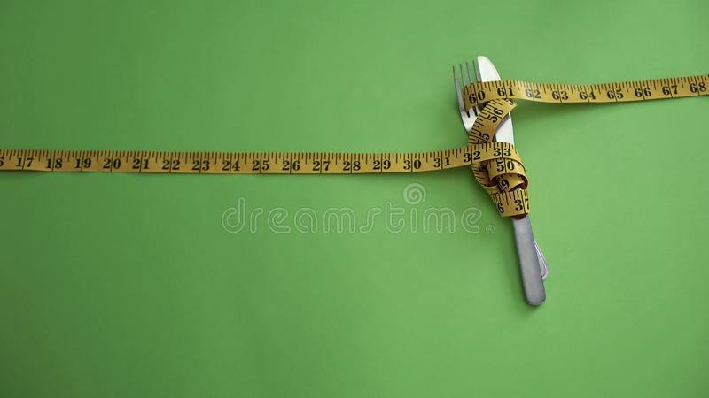 Het mes en de vork bonden met het meten van band, concept strikte voedselbeperkingen stock afbeeldingen