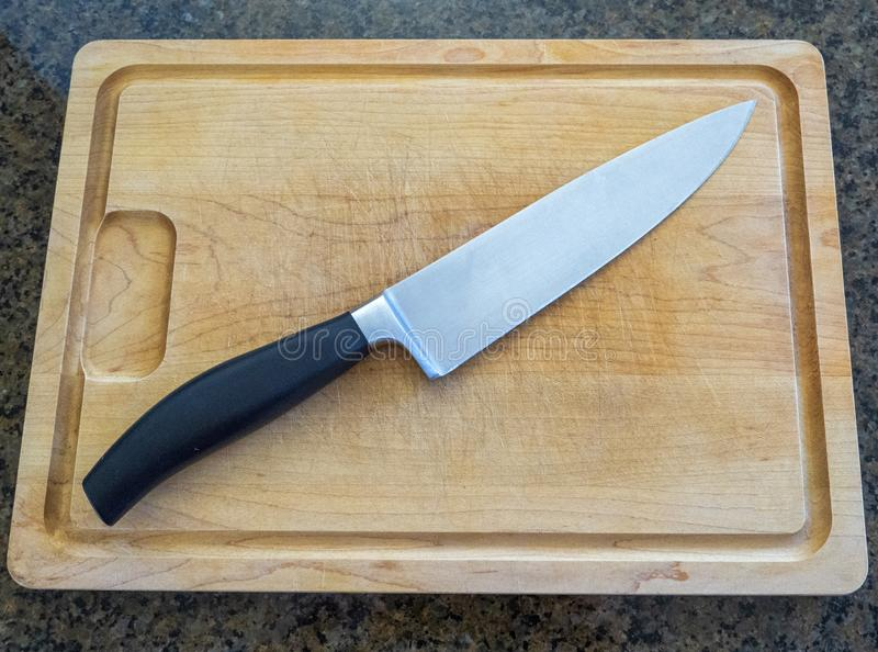 Het mes van de geïsoleerde grote chef-kok op een groot houten scherpe raad met een teller van de granietkeuken royalty-vrije stock afbeelding