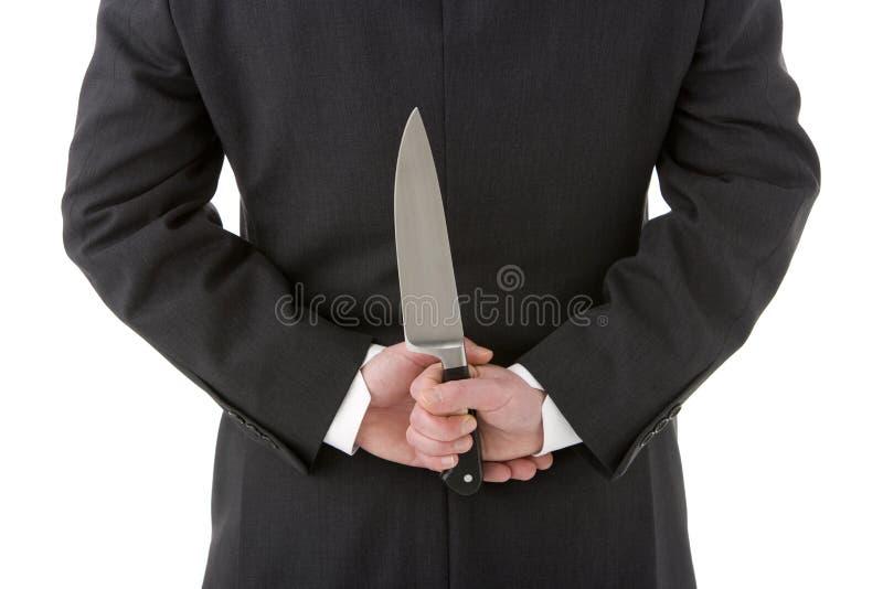 Het Mes van de Holding van de zakenman achter Zijn Rug stock foto