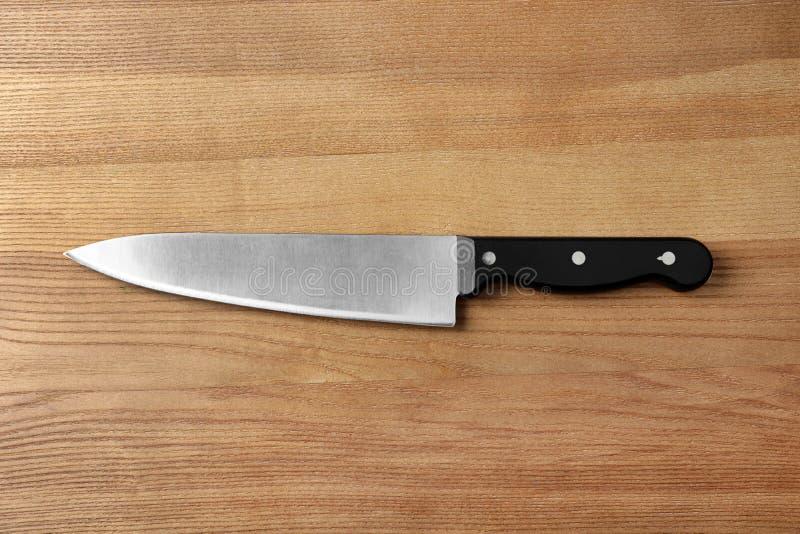 Het mes van de scherpe chef-kok op houten achtergrond stock afbeeldingen