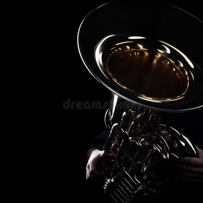 Het messingsinstrumenten van de tubaspeler stock afbeelding