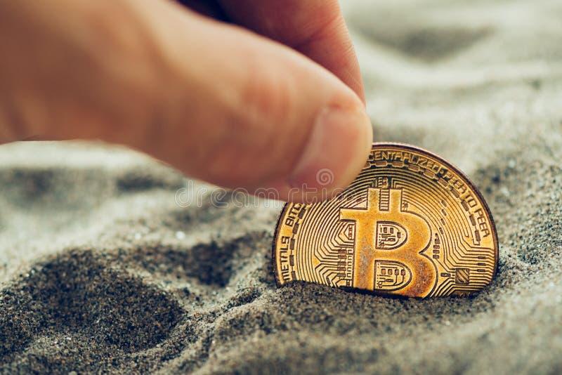 Het met de hand plukken van enige bitcoin van zand royalty-vrije stock foto's