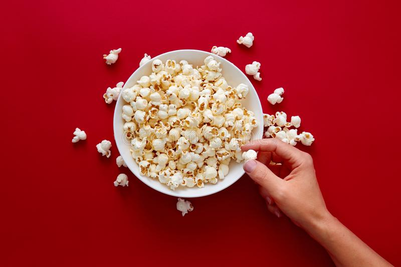 Het met de hand plukken van popcorn in witte kom royalty-vrije stock afbeelding