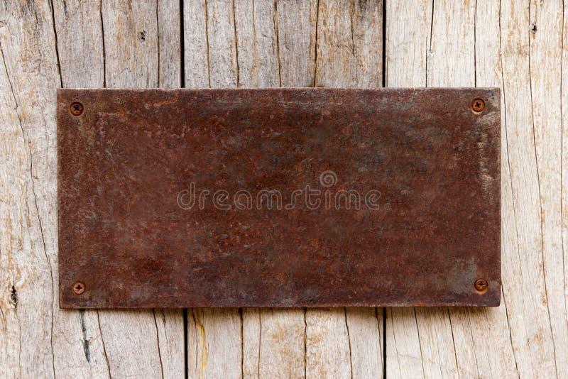 Het metaal heeft roest decoratieve plaat op hout stock foto
