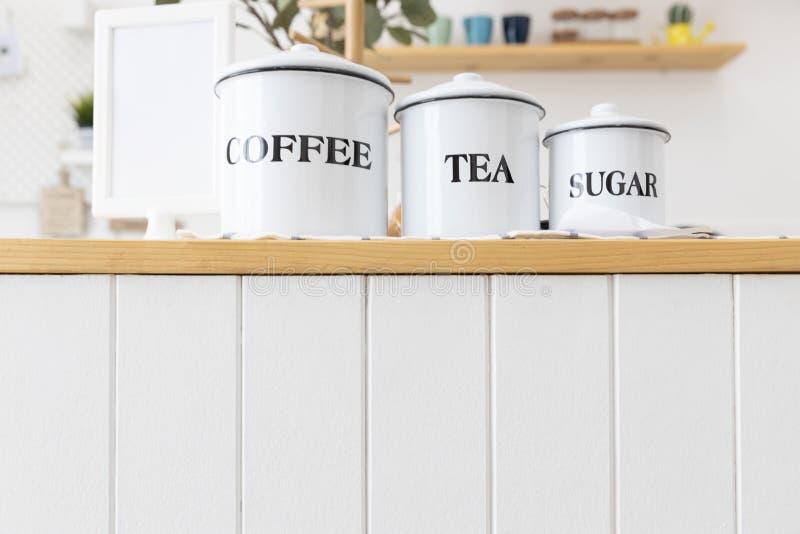 Het metaal kan van koffie, thee en suiker op houten tegenbar met witte muur stock afbeeldingen