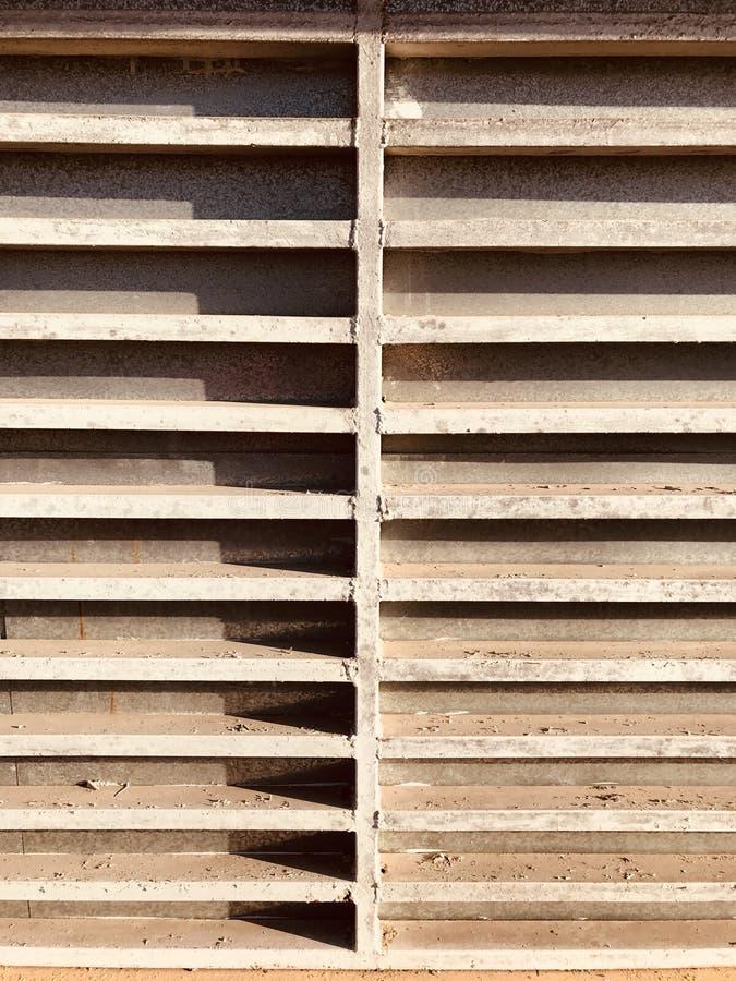 Het METAAL - SCHADUW - een geometrische kioskdeur behandelt een opslagvoorzijde tijdens gesloten uren - SLOOT - ROEST - LICHT stock afbeeldingen