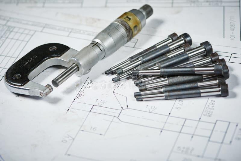 Het metaalbewerkende industrie en machinaal bewerken Details met het meten van micrometer op druktekening stock foto