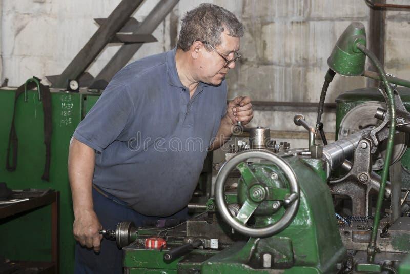 Het metaalbewerkende werk van winkelarbeiders achter machines en apparaten om staalstructuren tot stand te brengen kharkov stock afbeeldingen