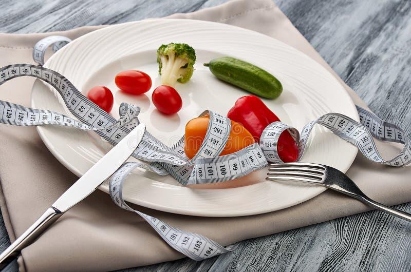 Het meten van band in een plaat met verse groenten stock foto