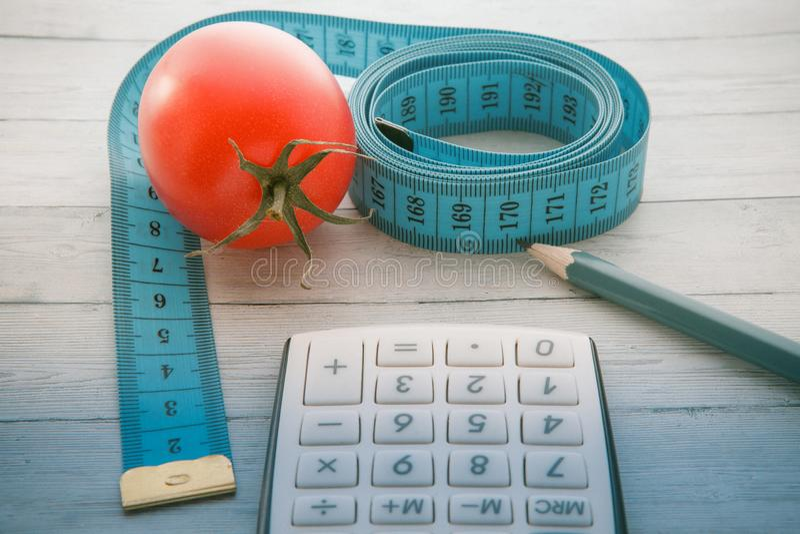 Het meten van band en calculator met sappige tomaat, concept het gezond eten en vermageringsdieet, close-up stock foto's