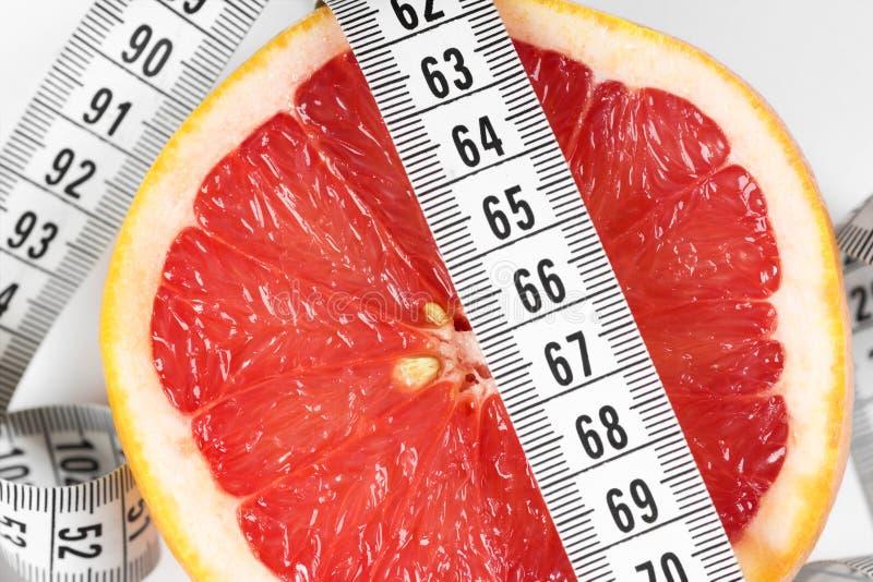 Het meten van band met grapefruit stock afbeeldingen