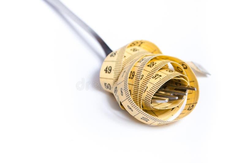 Het meten van band op een vorkconcept stock fotografie