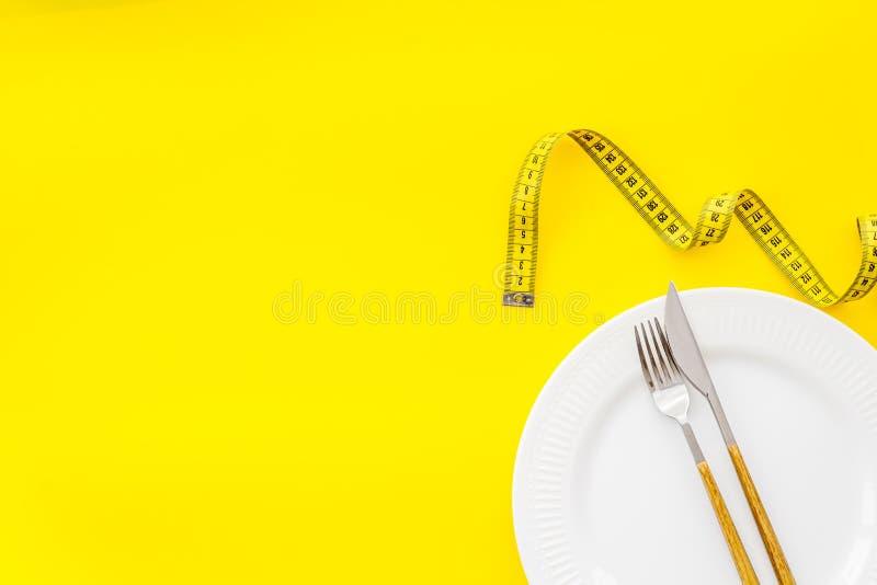 Het meten van band, plaat met vork en mes op geel achtergrond hoogste meningsmodel royalty-vrije stock foto