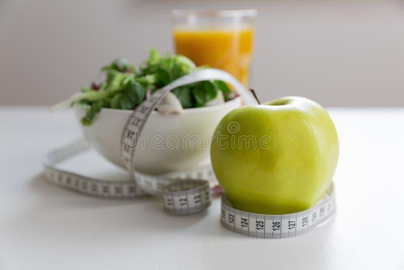 Het meten van band rond de appel, kom groene salade en glas sap Gewichtsverlies en juist voedingsconcept stock foto