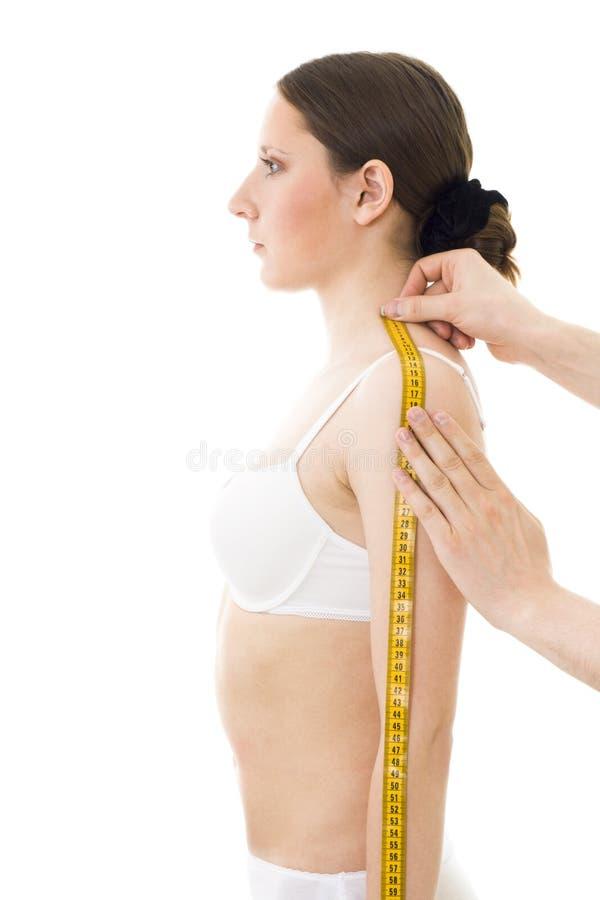 Het meten van de schouderlengte van de vrouw stock foto