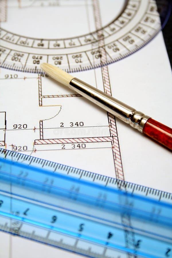 Het meten van heersers en kunstborstel op een document met het plan stock afbeelding