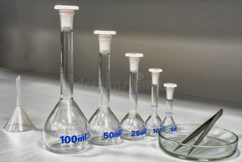 Het meten van laboratoriumglaswerk met forceps royalty-vrije stock afbeeldingen