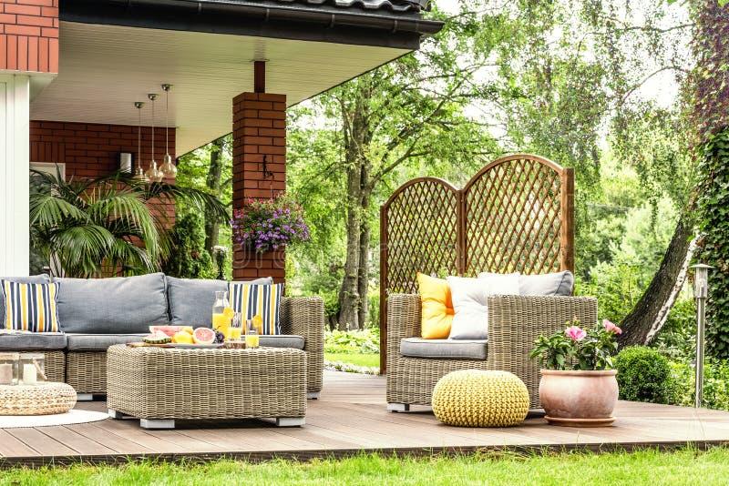 Het meubilair van de rotantuin met grijze hoofdkussens, lijst met fruit op a royalty-vrije stock afbeeldingen