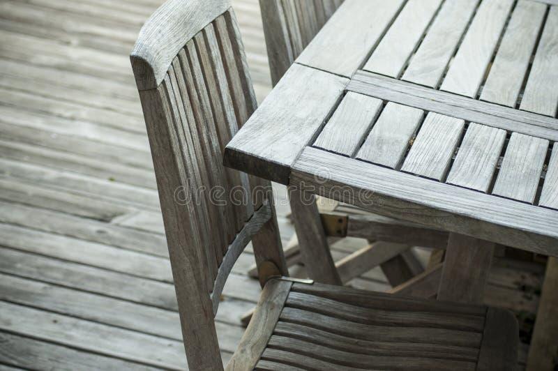 Het meubilair van de teaktuin op een houten terras in de lente stock fotografie