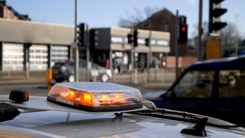 Het middel van de dagmening van flitser van het noodsituatie de lichte baken op dak van onderhoudsauto wordt geschoten op Britse  stock foto