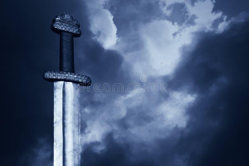 Het middeleeuwse zwaard van Viking tegen een dramatische hemel stock foto's